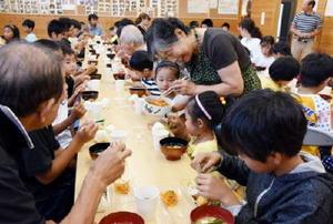 この夏最後のラジオ体操を終えた朝食会で、ニンジンのおかずをもらう子どもたち=佐賀市の坂井公民館