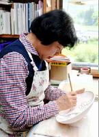 一気呵成(かせい)に筆を走らせて生命の躍動感を表現する岡部美智子さん=西松浦郡有田町のけいこう窯