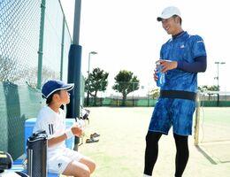 練習の合間に父・勲さん(右)と話す高木咲來ちゃん=久留米市の新宝満川テニスコート