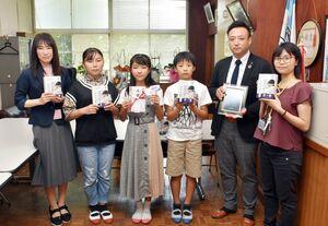 槙原校長(左)と児童代表らに非接触型体温計を贈ったアルミスの余田社長(右から2人目)=鳥栖市の田代小