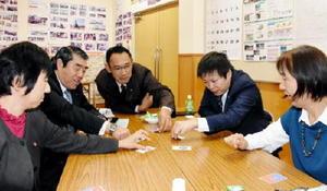 カードゲーム「クロスロード」で防災対応を学ぶ議員たち=伊万里市の立花公民館