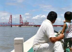船の先端で昇開橋を眺める参加者ら