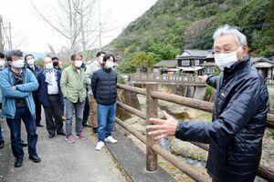 河口純一名誉会長(右)の案内で有田川ののり面の泉山陶石を見学する会員ら=有田町大野