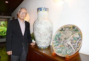 高柳快堂が絵付けした「色絵山水図大花瓶」(左)と「色絵鷹図皿」を里帰りさせた明治伊万里研究所の蒲地孝典代表=有田町のギャラリー花伝