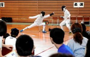 参加者らにフェンシングの実演を披露する競技団体=佐賀市の県総合体育館