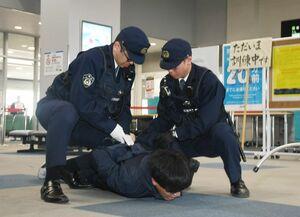 テロ対処訓練で犯人を制圧する警察官=佐賀市の佐賀空港