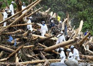 大量に積み重なった流木の上で、捜索活動をする警察官ら=9日、福岡県東峰村