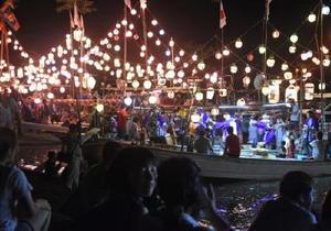 鉦や笛を鳴らして浮立を競演する漁船を、夏祭りに参加した人々が見守った=鹿島市の七浦海浜スポーツ公園