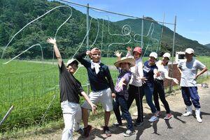 イノシシ防護柵を利用したイルミネーションを設置する地元住民と佐賀大学生=伊万里市東山代町川内野