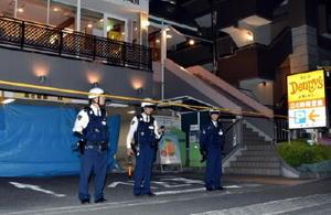 発砲事件があったファミリーレストランの駐車場前を警戒する警察官=30日午前0時10分ごろ、神奈川県座間市