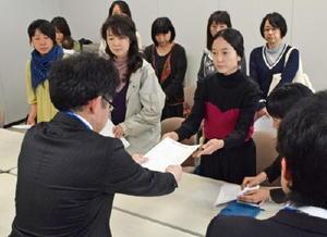 再稼働に同意しないよう求める要請書と質問書を、県の担当者に手渡す福岡県糸島市などの母親たち=佐賀県庁