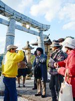 磁器製の鳥居の説明を聞く参加者=有田町の陶山神社