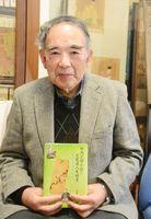 出版した本を手にする松尾和義さん=鹿島市の自宅