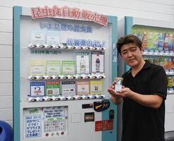 昆虫食の自動販売機と古賀貴彦店長=みやき町のアクアシー
