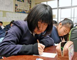 ニセ電話詐欺防止のために、祖父母に送る年賀状に言葉を書く児童たち=神埼市の仁比山小