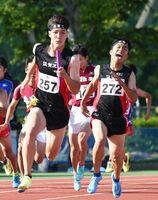 陸上男子400メートルリレー決勝 佐賀工・第3走者の吉田享介(右)からバトンを受け走り出すアンカーのフェルナー英輝=佐賀市のSAGAサンライズパーク運動場補助競技場