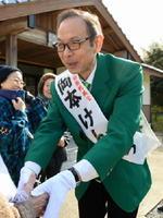 緑のジャケットを着て、支持者らと握手を交わす岡本憲幸候補=唐津市相賀