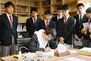 オリジナルの筆で極細の線を描く葉山さんを見つめる生徒たち=武雄市山内町のYUKIO HAYAMA STUDIO
