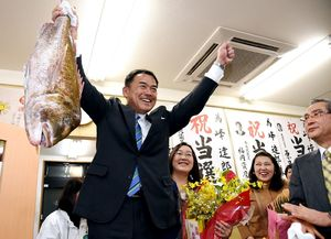 初当選し、支援者から贈られたタイを掲げる峰達郎市長=1月29日、唐津市町田の事務所