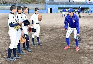 中学生に内野守備の指導をする岩本忠大選手(右)=伊万里市の国見台野球場