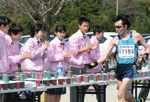 ランナー給水するボランティアの高校生たち=佐賀市大和町