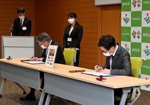 協定書に署名する脊振郵便局の廣瀧直義局長(右)と松本茂幸神埼市長=神埼市役所