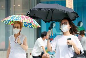 強い日差しの下、日傘を差して歩く人たち=7日午後、東京・銀座
