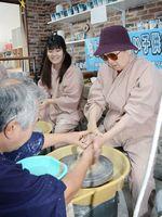 喜寿祝いで、ろくろで焼き物作りを体験する伊藤絹代さん=有田町の有田柳窯