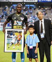 月間MVPに選ばれたイバルボ選手に記念パネルを渡す山口遥暉君(中央)。右は佐賀新聞社の井手研一販売局長