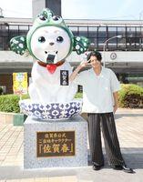 「佐賀春」像の横で「2(ピース)」のポーズをする小栗旬さん=佐賀市のJR佐賀駅(提供)