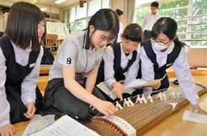 大神高の生徒(左から2人目)に琴の演奏法を教える上峰中の生徒たち。「さくらさくら」の演奏に挑戦した=上峰町の上峰中