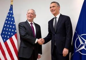 14日、ブリュッセルで行われたNATO国防相理事会で握手するストルテンベルグ事務総長(右)とマティス米国防長官(ロイター=共同)
