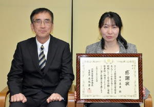 感謝状を受け取った中川真実さん(右)と夫の中川雅文巡査部長=佐賀市の佐賀県警本部