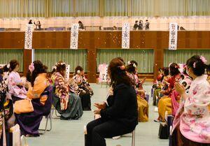 教職員がサプライズで準備した横断幕に拍手をして喜ぶ卒業生=佐賀市の佐賀女子短大