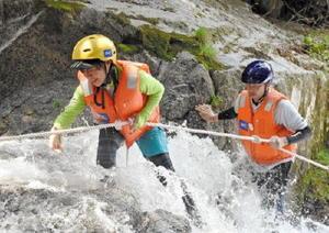 ロープを便りに流れに逆らって登る参加者=昨年7月、唐津市七山の滝川川
