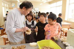 保存会の髙栁政廣さん(左)に人形の作り方を教わる児童ら=神埼市の西郷小