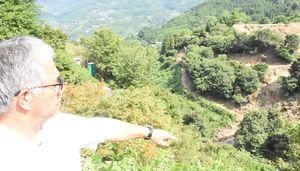 観音の滝から300メートルほど下流にある滝川川沿いの土砂崩れ。現場を対岸から指さす鬼木信義実行委員長=唐津市七山