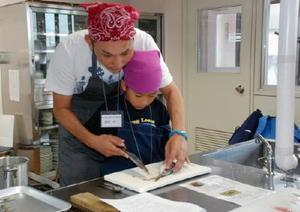 父子で協力しながら、アジの3枚おろしに挑戦する参加者=佐賀市の西九州大学佐賀調理製菓専門学校