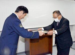 的野功署長(左)から感謝状を受ける神埼建設業協会の牟田正明会長=神埼市の神埼署