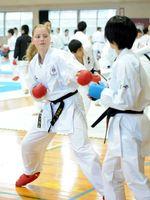 日本人選手とペアを組んで練習に励む海外の選手=佐賀市の大和勤労者体育センター