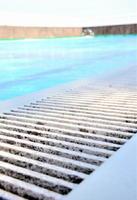 劣化し繊維が剥がれたとみられるプールサイドの排水溝のふた=9日、白石町の須古小