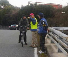 自転車の交通マナーについて外国人居住者に呼び掛ける補導員たち=基山町長野地区