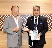 電話機を贈った廣島社長とペンダント型の子機を手に持つ秀島市長=佐賀市役所