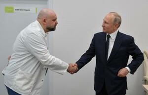 3月24日、モスクワ市内の感染症病院で、視察に訪れたプーチン大統領と握手するプロツェンコ医長(左)(タス=共同)