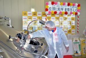 糖化槽と呼ばれるタンクに麦芽を投入する参加者=福岡県朝倉市のキリンビール福岡工場