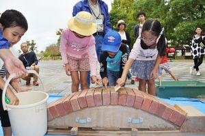 レンガを使ったアーチ橋づくりに挑戦する子どもたち=佐賀市の県立森林公園