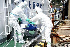 感染者役の男性を巡視艇から下ろす訓練参加者たち=唐津市呼子町の呼子港