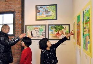松梅校小学部の子どもたちが地元の景色を描いた60点が並ぶ会場=佐賀市大和町松瀬の湛然の里ぎゃらり「せせらぎ」