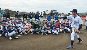 スローイングを手本を見つめる少年野球の選手たち=唐津市の松浦河畔公園野球場