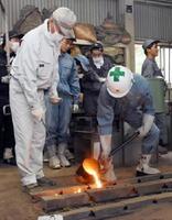 約1400度まで熱して溶けた鉄を型に流し入れる生徒=佐賀市の佐賀工高